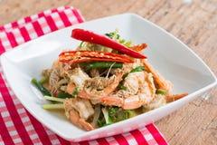 Crevette faite sauter à feu vif avec le curry dans le plat blanc sur le bois brun photographie stock