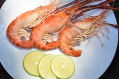 Crevette grillée avec le citron du plat blanc sur la table en bois, fruits de mer Image libre de droits