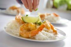 Crevette thaïlandaise de tigre avec des pâtes de riz et limons avec le doigt évident Photographie stock libre de droits