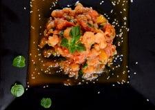 Crevettes avec la tomate et le basilic du plat noir Image stock