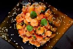 Crevettes avec la tomate et le basilic du plat noir Photo stock