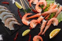 Crevettes crues et bouillies d'un plat en pierre images stock