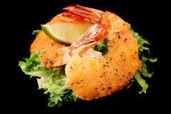 Crevettes cuites à la friteuse avec de la laitue d'isolement sur le noir Photo libre de droits