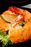 Crevettes cuites à la friteuse avec de la laitue du plat noir Images stock