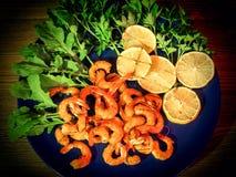 Crevettes et citron grillés avec les verts, l'arugula et le persil sur un plat bleu photos libres de droits