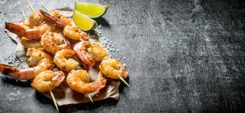 Crevettes frites sur des brochettes avec des tranches de chaux photo stock