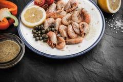 Crevettes grillées avec de la sauce et des légumes du plat en céramique Image stock