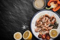 Crevettes grillées avec des légumes et assaisonnement du plat en céramique Photo libre de droits
