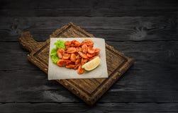 Crevettes grillées sur un conseil au-dessus de fond en bois foncé Images stock