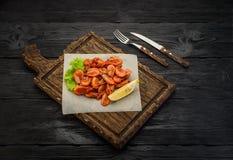 Crevettes grillées sur un conseil au-dessus de fond en bois foncé Photo libre de droits