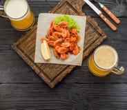 Crevettes grillées sur une tasse de conseil et de bière Photographie stock libre de droits