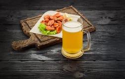Crevettes grillées sur une tasse de conseil et de bière Table en bois foncée Photographie stock libre de droits