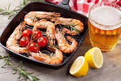 Crevettes grillées sur la poêle et la bière Images stock