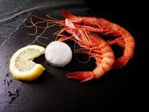 Crevettes roses, citron et glace rouges Plat noir, l'espace pour la copie Image stock