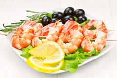 Crevettes roses de tigre sur une brochette avec des olives Photo stock