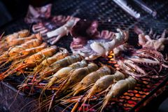 Crevettes roses et calmar grillés de roi sur le feu de BBQ Nourriture thaïlandaise de rue chez Chiang Mai Old City Night Market t image stock