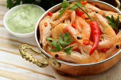 Crevettes roses frites avec des piments dans une casserole de cuivre Photographie stock