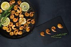 Crevettes roses frites de roi dans une poêle sur un fond noir images stock