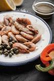 Crevettes roses grillées avec les câpres, la sauce et le poivron doux du plat en céramique Image libre de droits