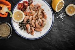 Crevettes roses grillées avec les tomates, le poivron doux et les câpres du plat en céramique Images libres de droits