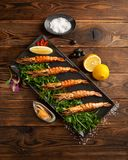 Crevettes roses grill?es argentines dans un plat noir sur le fond en bois photos stock