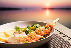 Crevettes roses, riz et coucher du soleil images stock