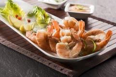 Crevettes roses, salade et immersions noires de tigre Image stock