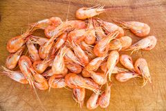 Crevettes rouges bouillies sur le plateau en bois Images libres de droits