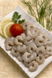 Crevettes sans tête crues crues avec la tranche et la tomate de citron du plat blanc avec mat en bambou photos stock