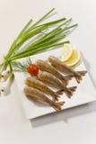 Crevettes sans tête enormes avec le citron et la tomate-cerise du plat blanc Images stock