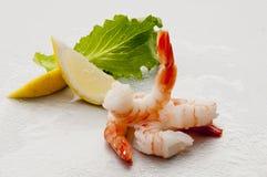 Crevettes sans tête enormes cuites à la vapeur avec les feuilles et le citron d'épicerie du plat blanc sur le fond blanc Photo libre de droits