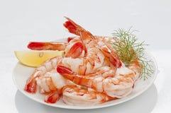 Crevettes sans tête enormes cuites à la vapeur avec les feuilles et le citron d'épicerie du plat blanc sur le fond blanc photographie stock