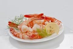 Crevettes sans tête enormes cuites à la vapeur avec les feuilles et le citron d'épicerie du plat blanc sur le fond blanc Photographie stock libre de droits