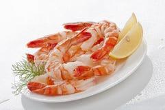 Crevettes sans tête enormes cuites à la vapeur avec les feuilles et le citron d'épicerie du plat blanc sur le fond blanc Images stock