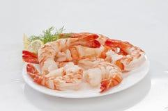 Crevettes sans tête enormes cuites à la vapeur avec les feuilles et le citron d'épicerie du plat blanc sur le fond blanc photos libres de droits