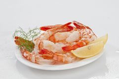 Crevettes sans tête enormes cuites à la vapeur avec les feuilles et le citron d'épicerie du plat blanc sur le fond blanc Images libres de droits