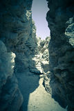 Crevice in the rock, forming a tunnel. tinted Royalty Free Stock Photo