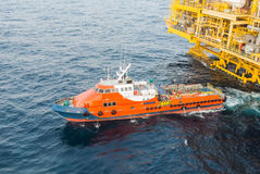Crew boat and oil platform yellow color. In the sea Royalty Free Stock Images