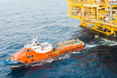Crew boat and oil platform yellow color. In the sea Stock Photo