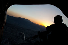 Crew Chief. Silhouette of a US Army CH-47 Chinook crew chief during a hard turn at sunset over Afghanistan royalty free stock photo