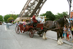 Crew. Horse-drawn carriage rolls of people near the Eiffel tower photo of 2012 Paris Stock Photography