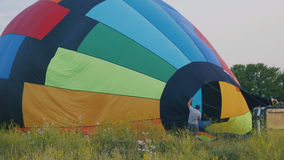 Crew inflate a big colorful hot air balloon at summer field Stock Images