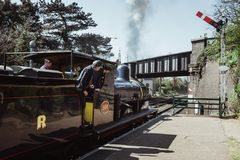 Crew looking out the cab on The Poppy Line steam train departing Sheringham, Nortfolk, UK stock image