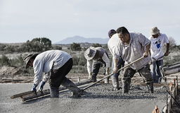 Crew of Masons working quickly to place and finish fresh concret Royalty Free Stock Photo