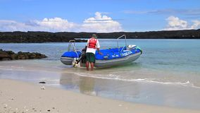 Crew member waiting for tourists with the dinghy on the beach of Chinese Hat island, Galapagos National Park, Ecuador stock footage