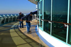 Crew Members cleaning windows. These two crewmen are cleaning the windows on a ship Royalty Free Stock Photography