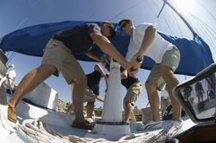 Crew Members Operating Windlass On Yacht stock image