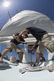 Crew Members Operating Windlass On Yacht. Low angle view of crew members operating windlass on yacht Stock Photos