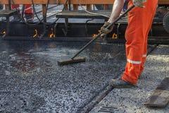 Crew placing mastic asphalt road Royalty Free Stock Image