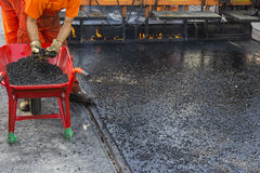 Crew placing mastic asphalt road and pea gravel surfacing Royalty Free Stock Image